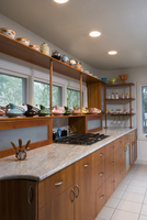 KITCHEN: Mid century modern , natural stained cabinets , light granite, open shelving with art pottery shelving with Red Wing pi