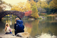 Rear view of a girl and a woman sitting on rocks along a river, New York City, New York State, USA