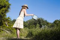 Side profile of a teenage girl watering plants 20025341134| 写真素材・ストックフォト・画像・イラスト素材|アマナイメージズ