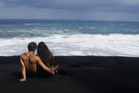 Rear view of a couple sitting on the beach, Kehena Beach, Big Island, Hawaii, USA