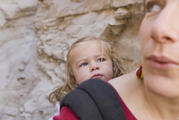 Close-up of a mid adult woman carrying her daughter in a baby carrier