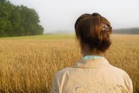 Rear view of a woman in a crop field