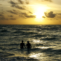 Silhouette of a couple standing in the sea at dusk