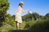 Side profile of a teenage girl watering plants 20025341397| 写真素材・ストックフォト・画像・イラスト素材|アマナイメージズ