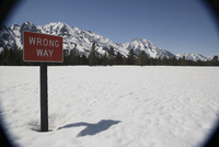 Sign post on a snow covered field with mountains in the background, Grand Teton National Park, Wyoming, USA