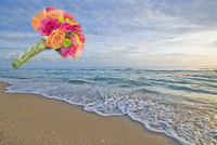 Bouquet of flowers in mid-air on the beach