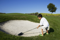 Boy working on a sand trap in a golf course