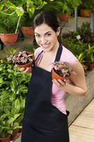 Woman holding potted plants in a greenhouse 20025341753| 写真素材・ストックフォト・画像・イラスト素材|アマナイメージズ