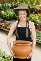 Woman holding a pot in a greenhouse 20025341785| 写真素材・ストックフォト・画像・イラスト素材|アマナイメージズ