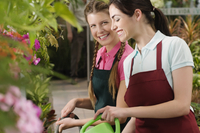 Two women watering plants in a greenhouse 20025341796| 写真素材・ストックフォト・画像・イラスト素材|アマナイメージズ
