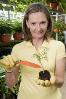 Woman holding a sapling in a greenhouse 20025341807| 写真素材・ストックフォト・画像・イラスト素材|アマナイメージズ