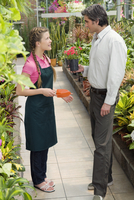 Customer buying a potted plant in a greenhouse