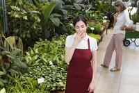Woman yawning in a greenhouse 20025341843| 写真素材・ストックフォト・画像・イラスト素材|アマナイメージズ