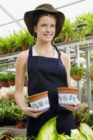 Woman holding pots in a greenhouse 20025341861| 写真素材・ストックフォト・画像・イラスト素材|アマナイメージズ