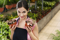 Woman holding potted plants in a greenhouse 20025341885| 写真素材・ストックフォト・画像・イラスト素材|アマナイメージズ