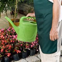 Man holding a watering can in a greenhouse