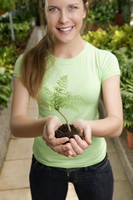 Woman holding a sapling in a greenhouse