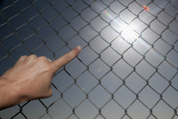 Person pointing towards the sun through chainlink fence