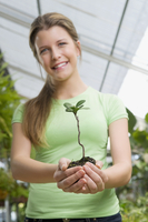 Woman holding a sapling in a greenhouse 20025342081| 写真素材・ストックフォト・画像・イラスト素材|アマナイメージズ