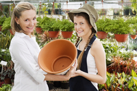 Female planter giving pot to customer in a greenhouse 20025342113| 写真素材・ストックフォト・画像・イラスト素材|アマナイメージズ