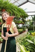 Woman holding a rake in a greenhouse 20025342125| 写真素材・ストックフォト・画像・イラスト素材|アマナイメージズ