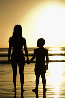 Silhouette of a woman with her son standing on the beach