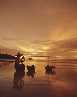 Woman with lamp and baskets on the beach, Phuket, Thailand