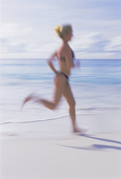 Blurred motion image of a woman jogging on the beach, Mahe Island, Seychelles, Indian Ocean, Africa