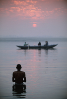Boat passing a man standing in the holy river , River Ganges (Ganga), Varanasi (Benares), Uttar Pradesh state, India, Asia
