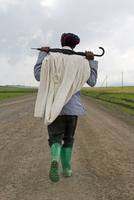Man walking along the road during the rainy season wearing green boots and holding an umbrella, The Ethiopian Highlands, Ethiopi 20025347854| 写真素材・ストックフォト・画像・イラスト素材|アマナイメージズ
