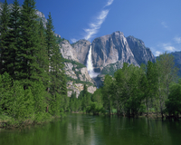 The Merced River swollen by summer snowmelt, with the Yosemite Falls in the background, in the Yosemite National Park, UNESCO Wo