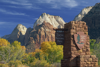 Sign at south entrance to the Park, trees in fall colours, and the Mountain of the Sun and the Twin Brothers peaks, in the Zion