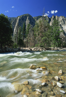 Rocks in the South Fork of the Kings River, with trees and crags in the background, in Cedar Gorge, Kings Canyon National Park,