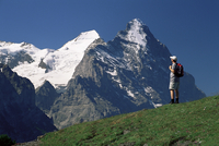 Hiker looking to the snow-covered Monch and the north face of the Eiger, Gross Scheidegg, Grindelwald, Bern, Swiss Alps, Switzer