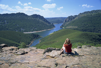 Walker at Cerro Gimio viewpoint looking to lake and hills in the Monfrague Natural Park, Caceres, Extremadura, Spain, Europe