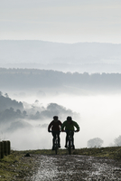 Two mountain bikes climbing up hill, silhouetted against mist, Newlands Corner, near Guildford, Surrey Hills, Surrey, England, U