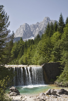 View across waterfall over weir on River Velika Pisnca to Prisank mountain, Triglav National Park, Julian Alps, Kranjska Gora, D