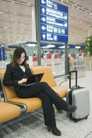 A Chinese business woman using a laptop computer at Beijing Capital Airport, part of new Terminal 3 building opened February 200