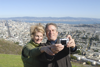 Married couple take photo of themselves, with downtown San Francisco beyond, California, United States of America, North America 20025350801| 写真素材・ストックフォト・画像・イラスト素材|アマナイメージズ