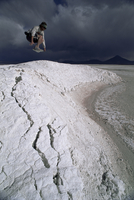 Jumping above the borax deposits on borders of Laguna Colorado, Bolivia, South America