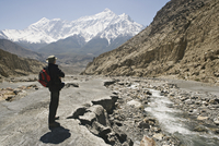 Trekker enjoys the view on the Annapurna circuit trek, Jomsom, Himalayas, Nepal. The high peak in the distance is 7021m Nilgiri,