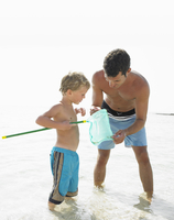 Father and son (6-8) in the surf holding fishing pole