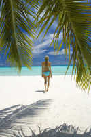 Young woman walking on beach, Maldives, Indian Ocean, Asia