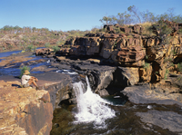 A man sitting on a rock up river, at the first stage of the Mitchell Falls in Kimberley, Western Australia, Australia, Pacific 20025352878| 写真素材・ストックフォト・画像・イラスト素材|アマナイメージズ