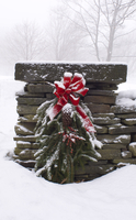 A snow covered Christmas wreath of pine branches, red berries and ribbon hanging on a stone wall, Rensselaervile, New York, Unit