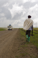 Man walking along the road during the rainy season wearing green boots and holding an umbrella, The Ethiopian Highlands, Ethiopi 20025353610| 写真素材・ストックフォト・画像・イラスト素材|アマナイメージズ