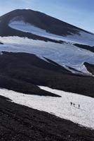 Walkers on snow field below steaming summit cone, Avacha volcano, 2741m high, Kamchatka, UNESCO World Heritage Site, Eastern Sib