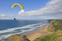 Paraglider with yellow wing above the south west coast of Portugal, Costa Vincentina, Praia do Castelejo and Cordama beaches nea