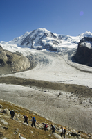 Hikers nearing ice flow of the Monte Rosa glacier, Zermatt Alpine Resort, Valais, Switzerland, Europe