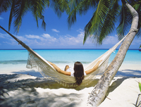 Woman sitting in hammock on beach, Maldives, Indian Ocean, Asia